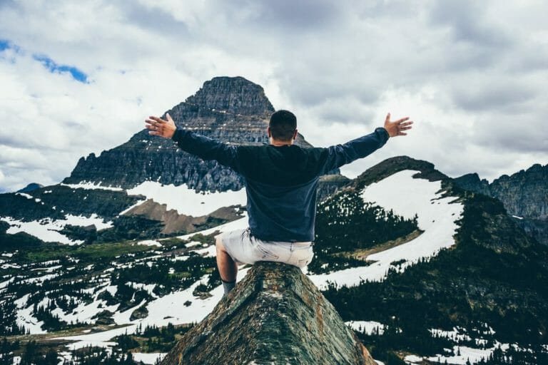Man on top of mountain with arms out, embracing the view and freedom